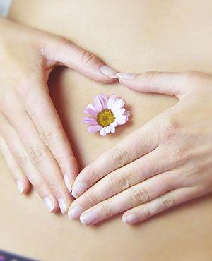 Schöner Bauch mit einer Blume in einem Schönheitssalon